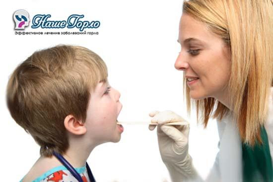 Врач проводит осмотр горла ребенка