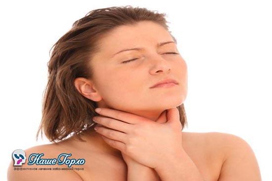 Девушка держится руками за шею из за боли в горле
