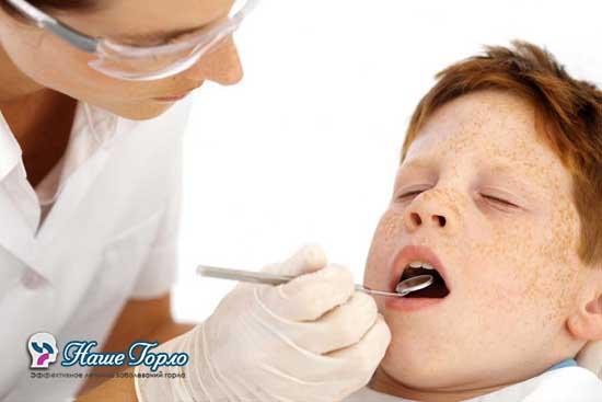 доктор осматривает ребенка носоглоточным зеркалом