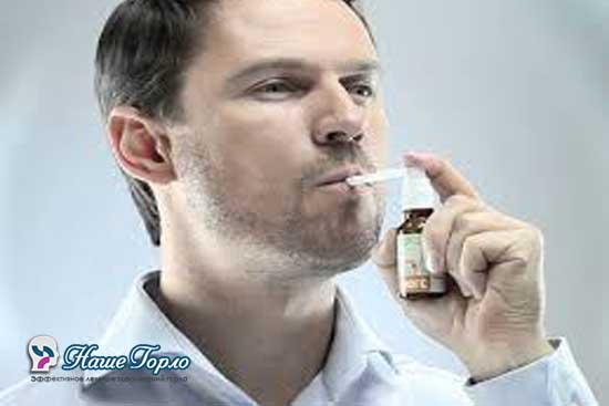 Мужчина использует спрей для горла