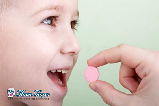 Ребенок пьет таблетку для горла
