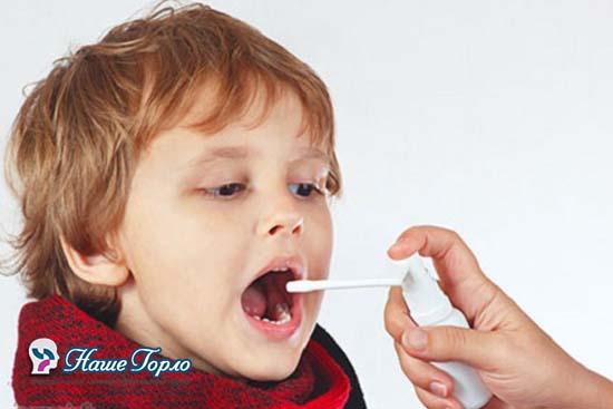 Ребенок брызгает горло спреем