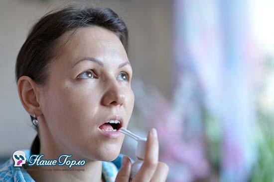 Женщина пользуется спреем для горла